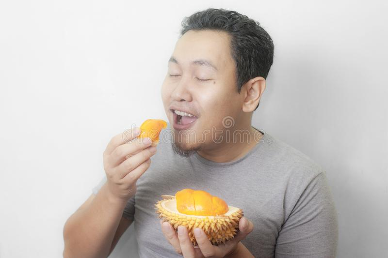 Funny Asian Man Enjoys Durian fruit. Portrait of funny Asian man enjoys yellow durian, king of fruit from Asia, stinky exotic food indonesian malaysian thai lai royalty free stock photo