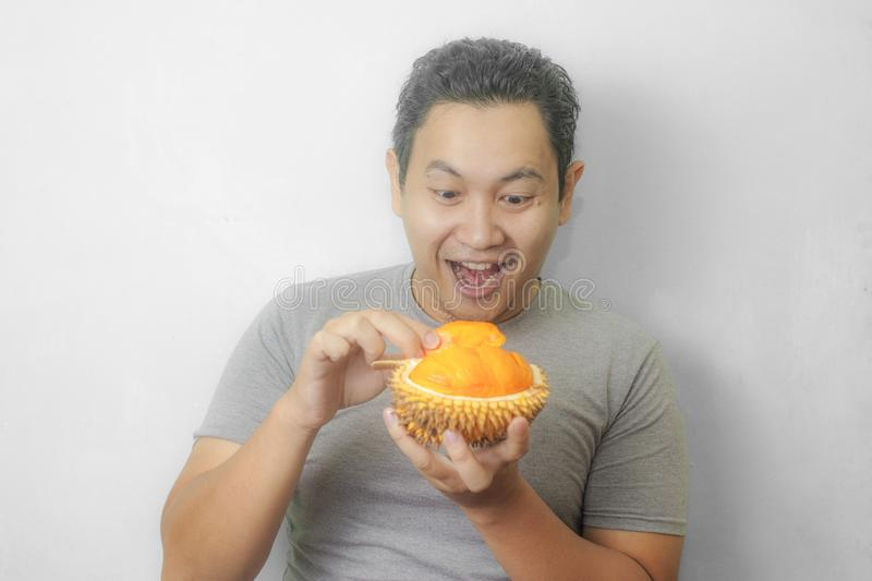 Funny Asian Man Enjoys Durian fruit. Portrait of funny Asian man enjoys yellow durian, king of fruit from Asia, stinky exotic food indonesian malaysian thai lai royalty free stock image