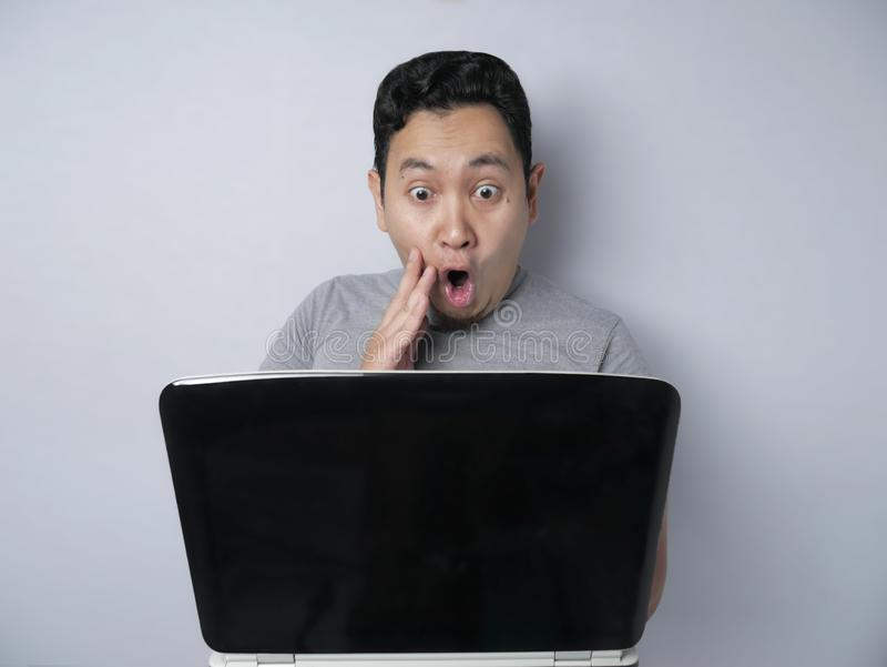 Funny Asian man shocked when Looking at His Laptop royalty free stock images