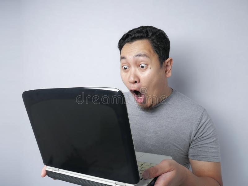 Funny Asian man shocked when Looking at His Laptop royalty free stock photo