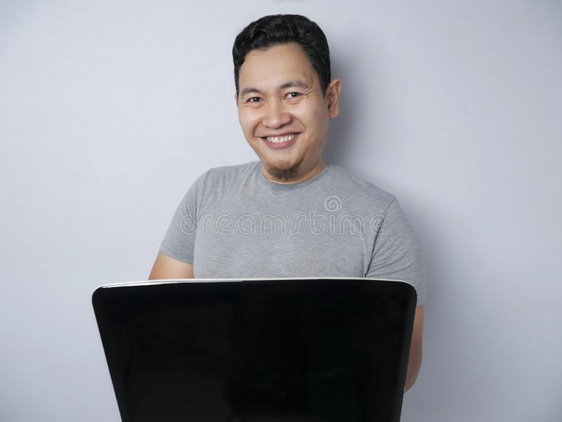 Funny Asian Man Working on His Laptop, Smiling Expression stock photos