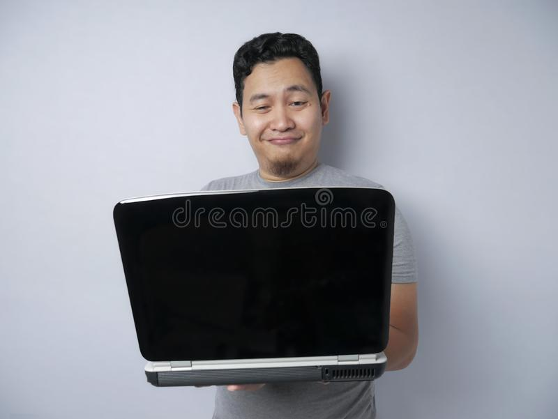Funny Asian Man Working on His Laptop, Smiling Expression stock photo