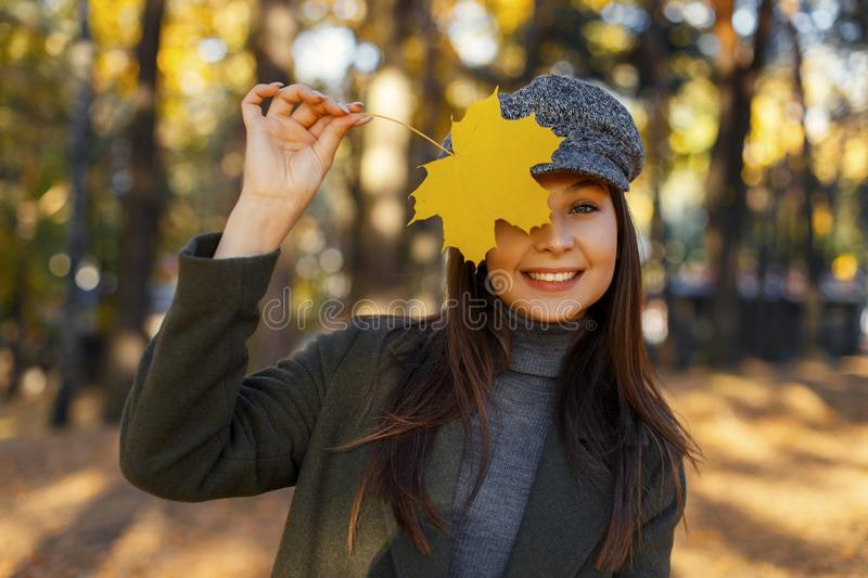 Funny attractive beautiful young happy woman with a smile in a vintage hat and coat covers her face with a yellow autumn leaf stock photos
