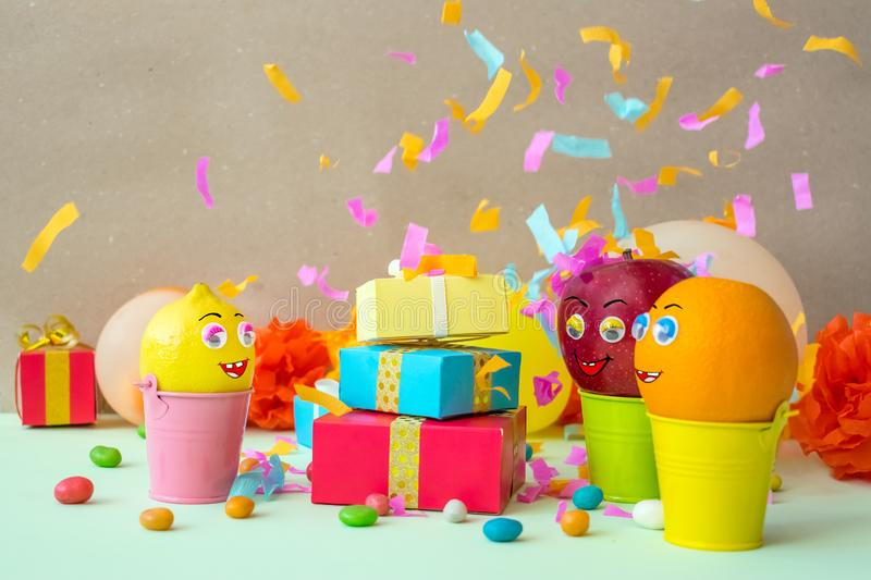 Funny attractive fruits with eyes and mouth - apple, orange, lemon, enjoy the gifts and dance on festive background. Summer party stock photo