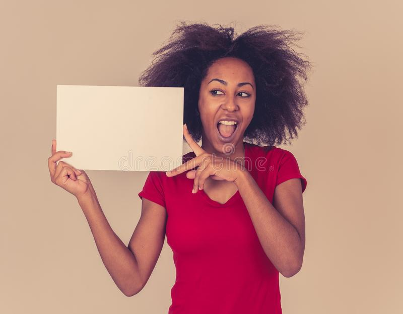Young funny and excited african american woman in red holding blank board for advertisement royalty free stock photos