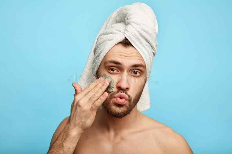 Funny awesome man with a towel on his head putting a mask on his face royalty free stock photo