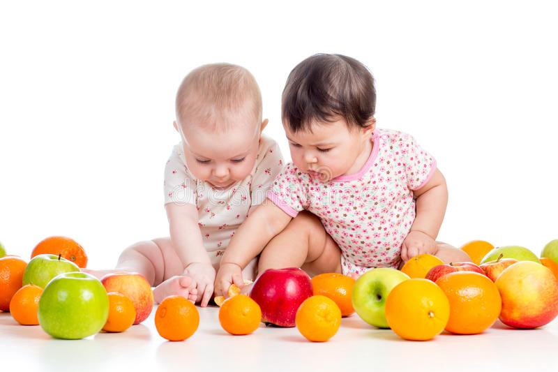 Funny babies eating healthy food fruits stock photography