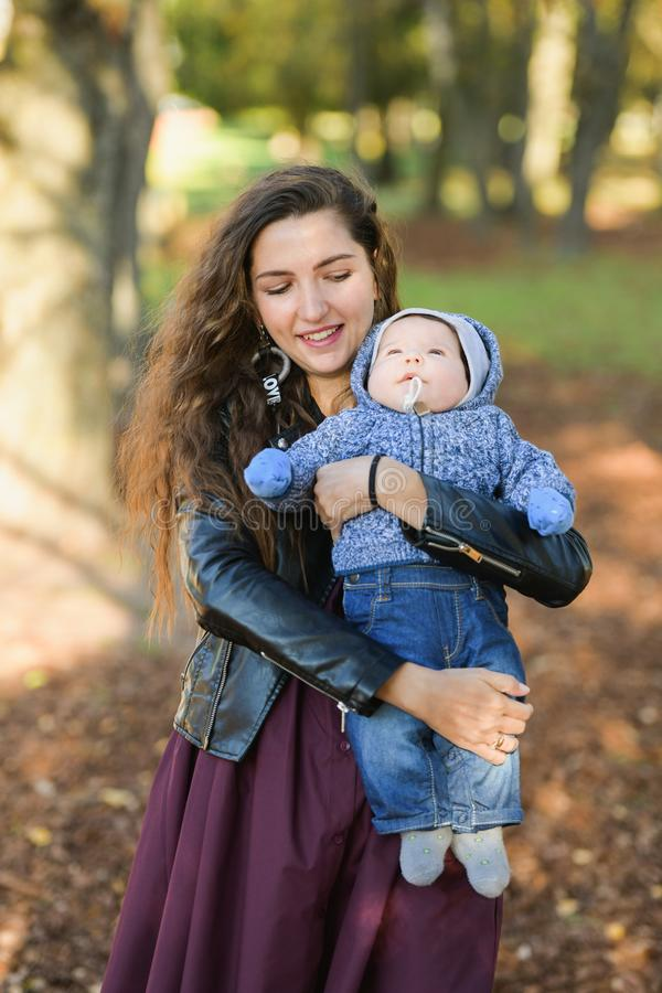Funny baby in the arms of mother. Attractive young woman mother with her son in her arms. Portrait of a happy mother and baby stock images