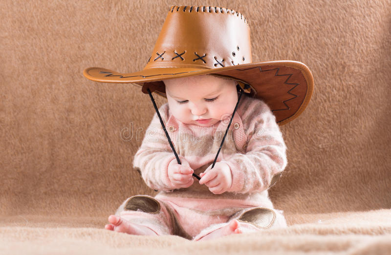 Funny baby in a big cowboy hat royalty free stock photo