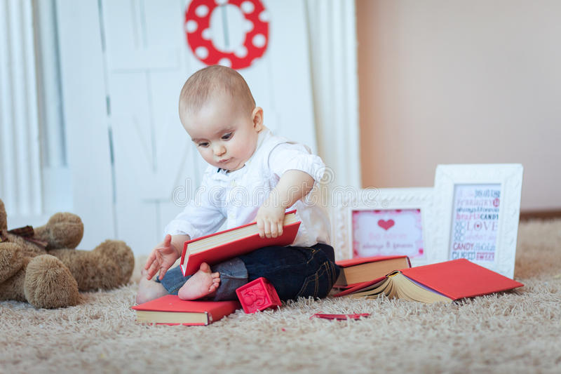 Funny baby with books. Funny cute baby playing with books on floor stock photo