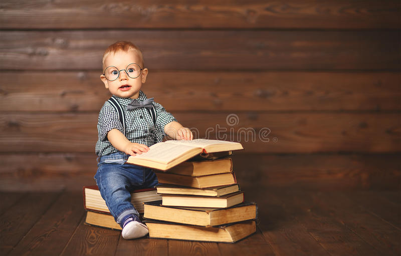 Funny baby with books in glasses royalty free stock image