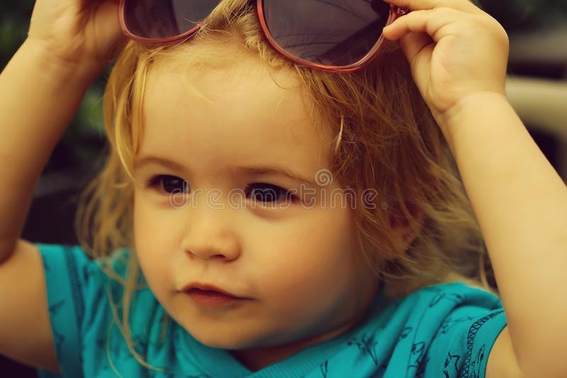 Funny baby boy with sunglasses. Funny baby boy child with curly blond hair and sunglasses on summer day at outdoor cafe stock photo