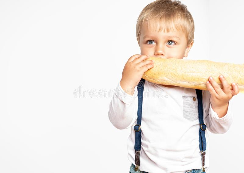 Funny baby boy eating a loaf of bread in studio. Tasty and fresh food. Bakery products royalty free stock images