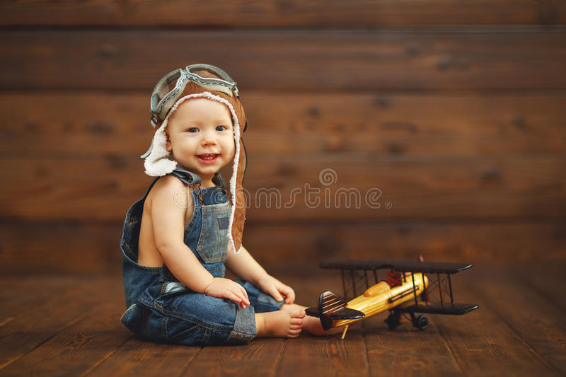 Funny baby boy pilot aviator with airplane laughing. On wooden background royalty free stock photos