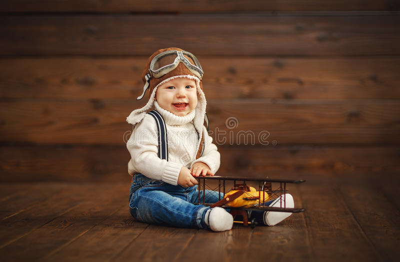 Funny baby boy pilot aviator with airplane laughing. On wooden background royalty free stock images