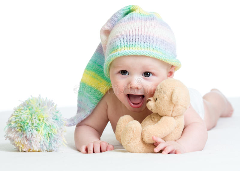 Funny baby boy with plush toy. Funny baby boy lying on bed with plush toy royalty free stock photography