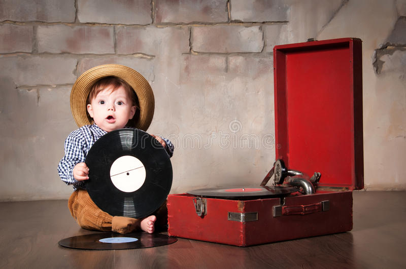 Funny baby boy in retro hat with vinyl record and gramophone stock image