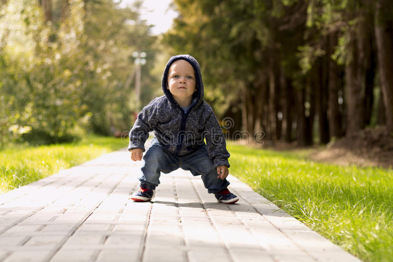 Funny baby boy squatting in the park. Autumn or summer shot.  royalty free stock photography