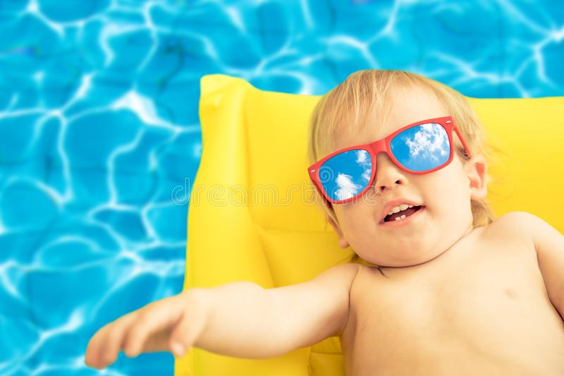 Funny baby boy on summer vacation. Child having fun in swimming pool royalty free stock image