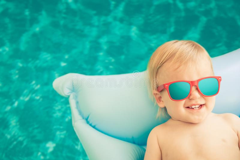 Funny baby boy on summer vacation. Child having fun in swimming pool royalty free stock photos
