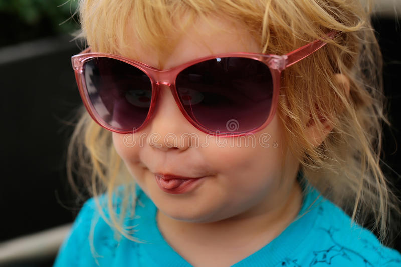 Funny baby boy in sunglasses. Funny baby boy child with curly blond hair grimaces in sunglasses on summer day at outdoor cafe royalty free stock photo