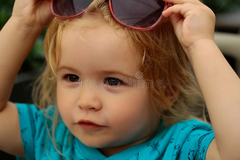 Funny baby boy with sunglasses. Funny baby boy child with curly blond hair and sunglasses on summer day at outdoor cafe royalty free stock photography