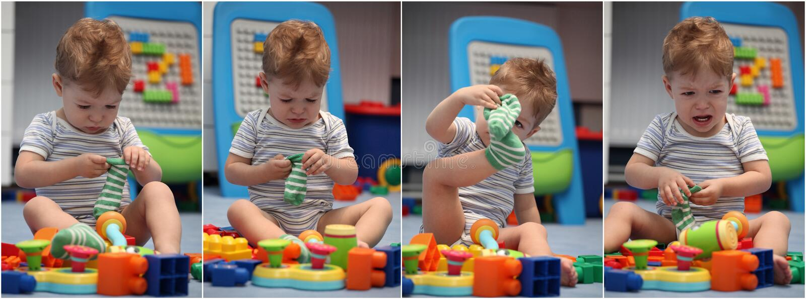A funny baby boy trying to dress socks stock photography