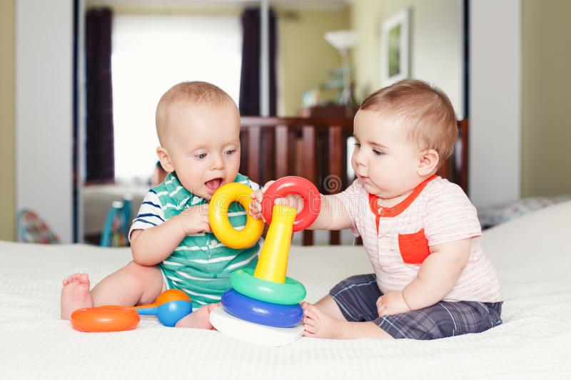 Funny baby boys sitting together on bed playing stacking rings toy. Group portrait of two white Caucasian cute funny baby boys sitting together on bed playing stock photos