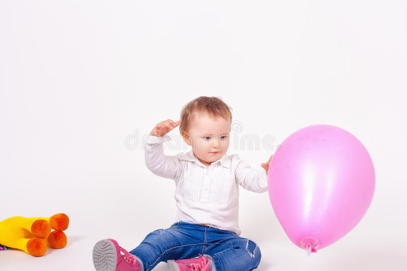 Funny baby celebrating first birthday. Balloon and toy stock image