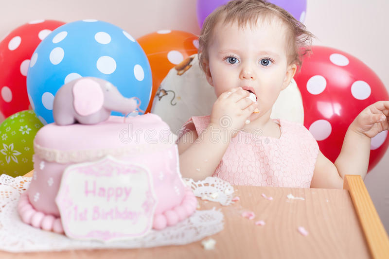 Funny baby celebrating first birthday and eating cake. Child with many balloons! Decoration at home. Make a first wish. Desire royalty free stock images