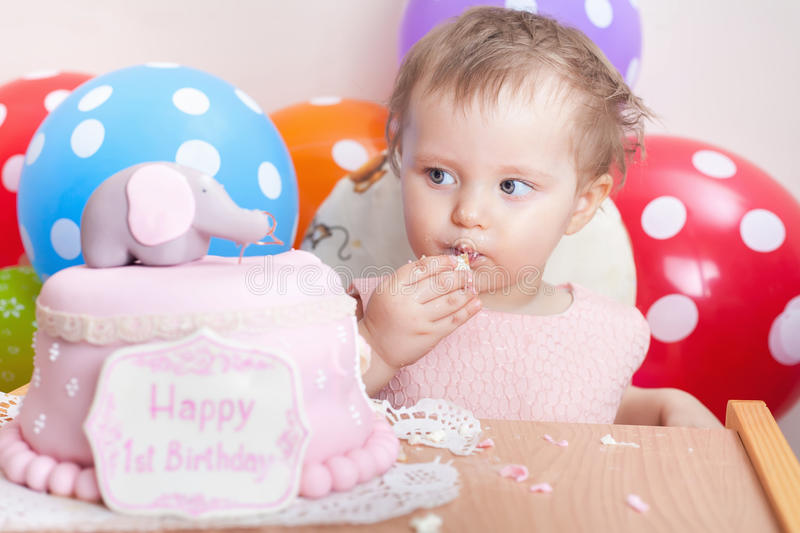 Funny baby celebrating first birthday and eating cake. Child with many balloons! Decoration at home. Make a first wish. Desire stock photos