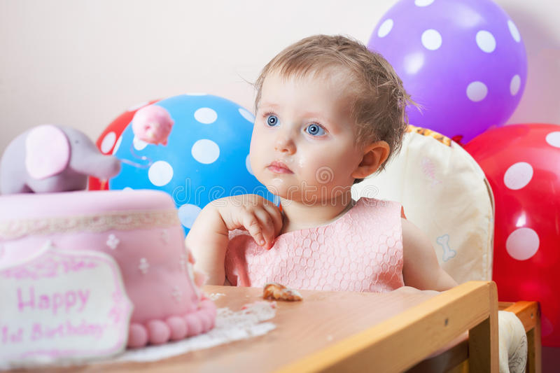 Funny baby celebrating first birthday and eating cake. Child with many balloons! Decoration at home. Make a first wish. Desire stock photography