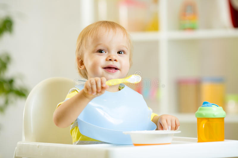 Funny baby child boy eating itself with spoon in. Funny cute baby kid boy eating itself with spoon in kitchen royalty free stock photo