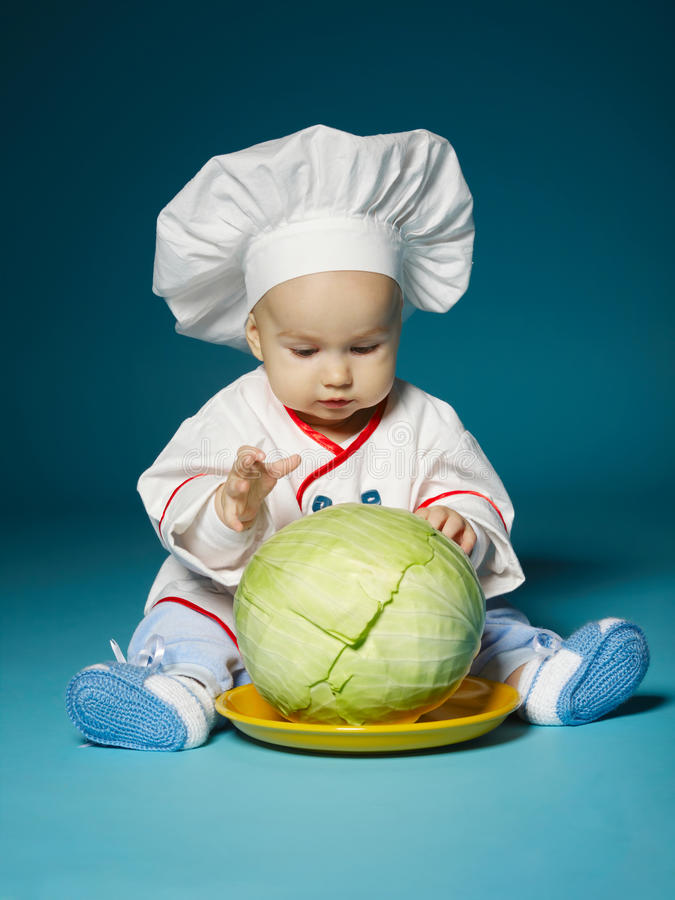 Funny baby with cook costume holds cabbage stock images