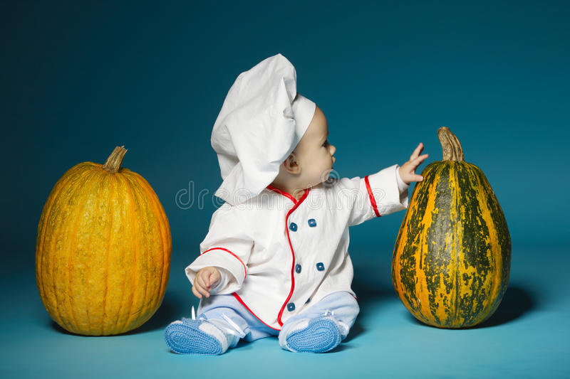 Funny baby with cook costume holds pumpkin royalty free stock photo
