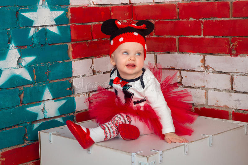 Funny baby girl. Little girl in a funny hat and red skirt stock photography