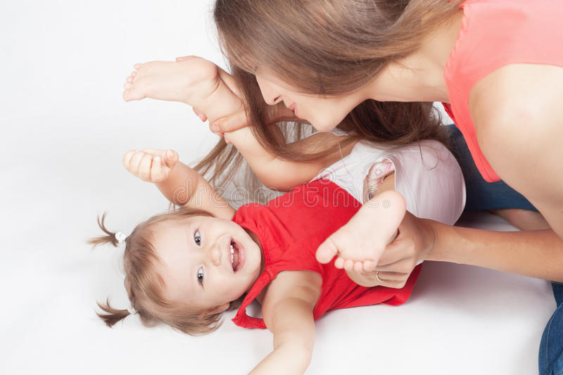 Funny baby girl lying near happy mother on white bed stock photos