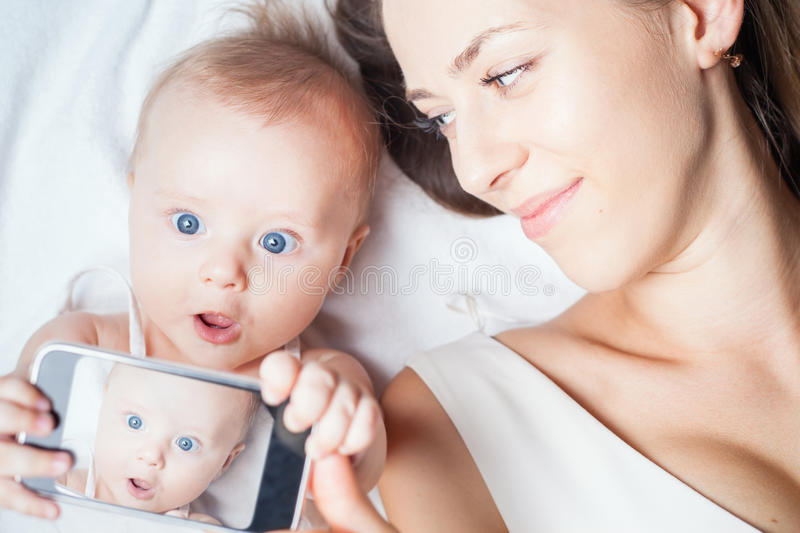 Funny baby girl with mom make selfie on mobile phone. Funny baby girl make selfie on mobile phone and lying near her mother on a white bed. Newborn looking at