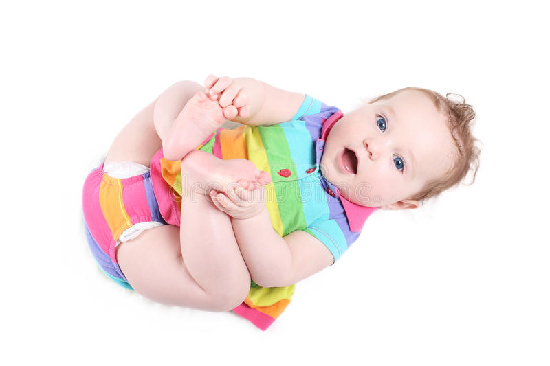 Funny baby girl playing with her feet royalty free stock photos