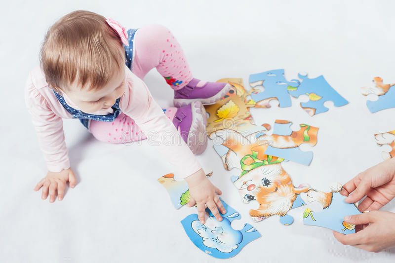 Funny baby girl playing with puzzle game for development stock image