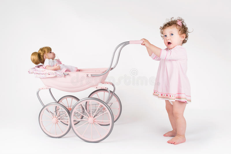 Funny baby girl walking with a doll stroller stock photos