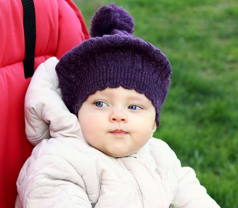 Funny baby in hat outdoor sitting stock image