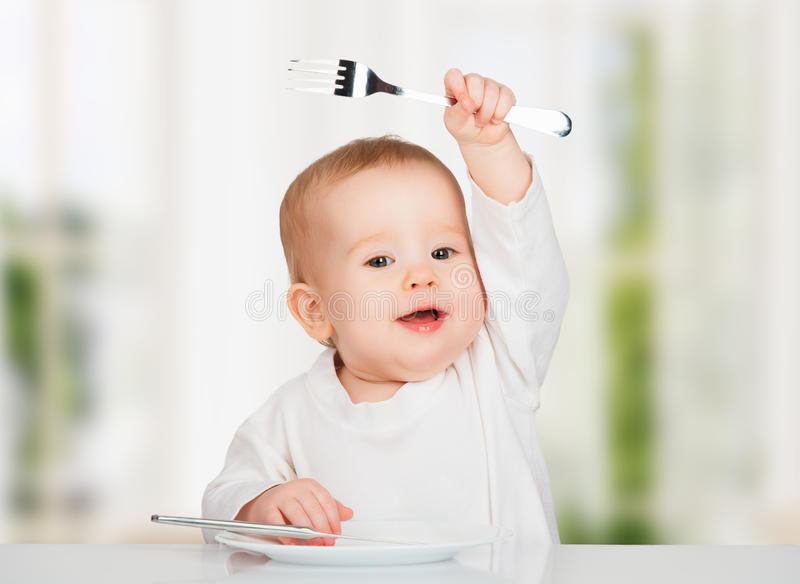 Funny baby with a knife and fork eating food. Funny happy baby with a knife and fork eating food royalty free stock photos