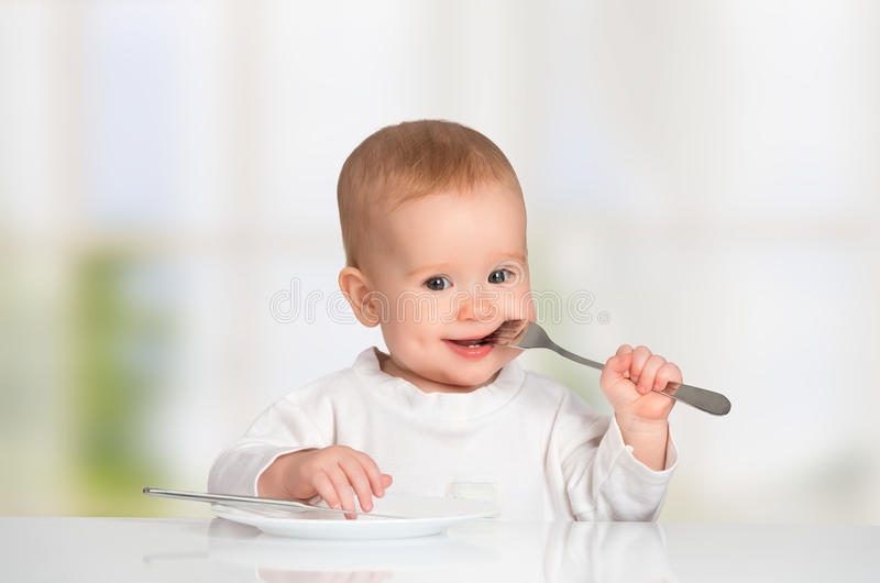 Funny baby with a knife and fork eating food royalty free stock image