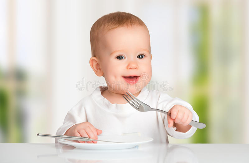 Funny baby with a knife and fork eating food stock photos