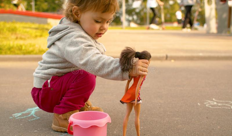 Funny baby playing with a doll. Against skate park royalty free stock photos