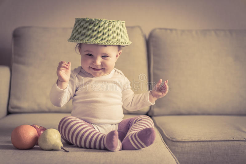Funny baby plays with dish and fruit royalty free stock images