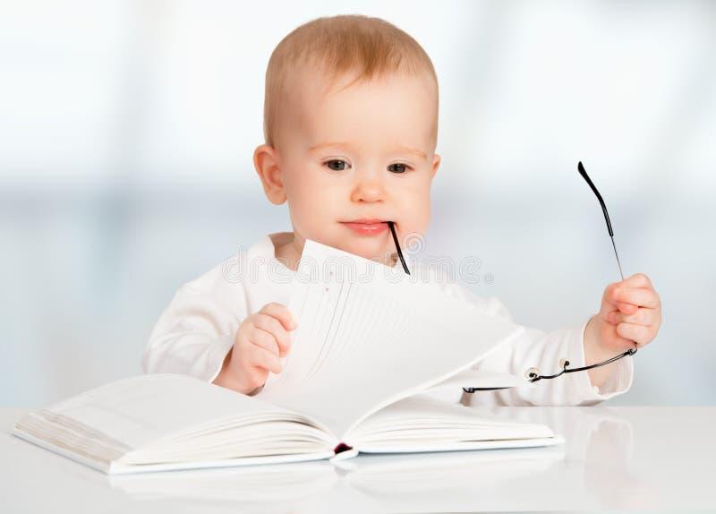 Funny baby reading a book stock photos