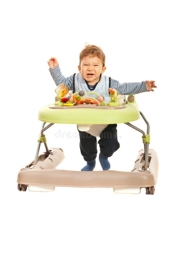 Funny baby running in walker stock image