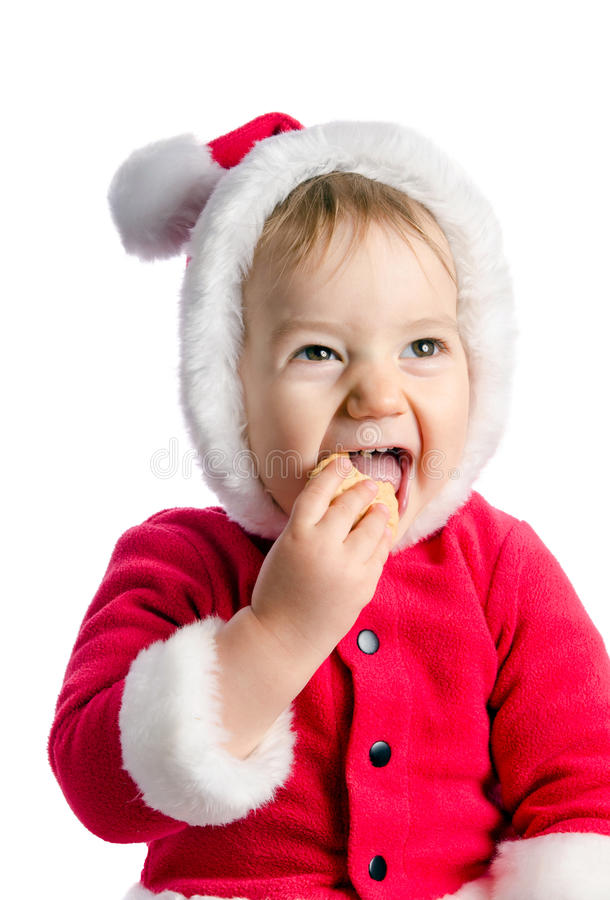 Funny baby in Santa Claus clothes eats cracker. On white background royalty free stock photo